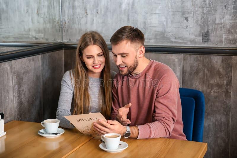 看通过菜单的年轻夫妇在餐馆 免版税库存图片