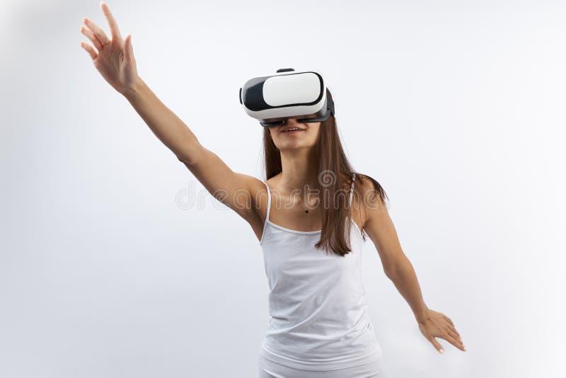 看通过虚拟现实耳机,在白色背景的室内射击的可爱的少妇 看起来女性mod的专家 库存图片
