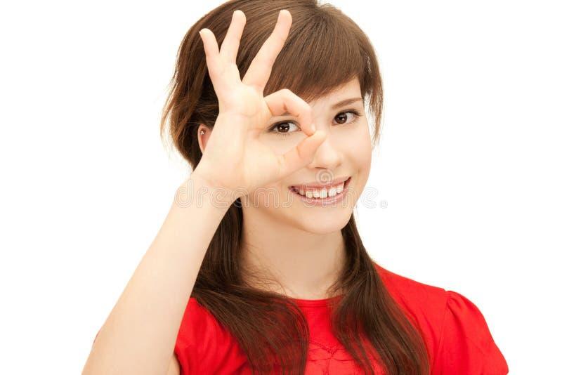 看通过从手指的孔的十几岁的女孩 库存图片