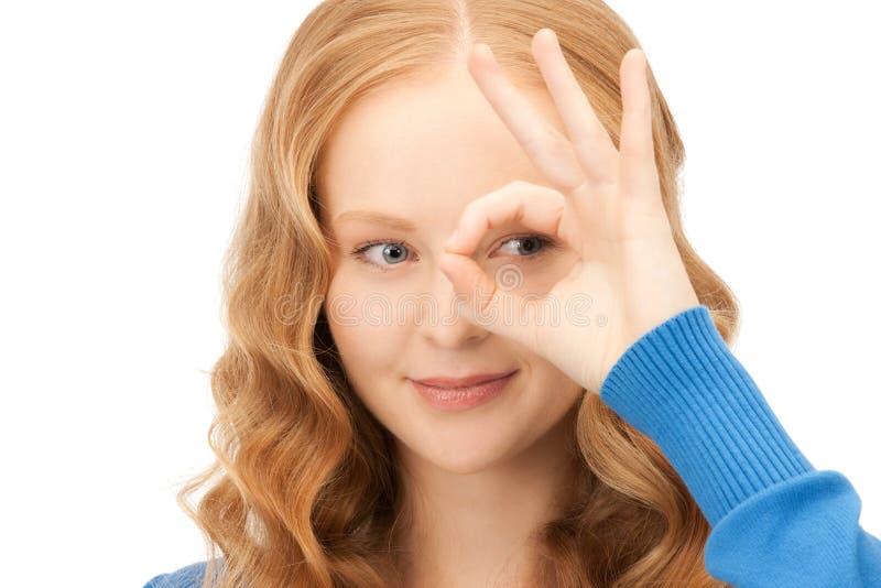 看通过从手指的孔的可爱的妇女 免版税图库摄影