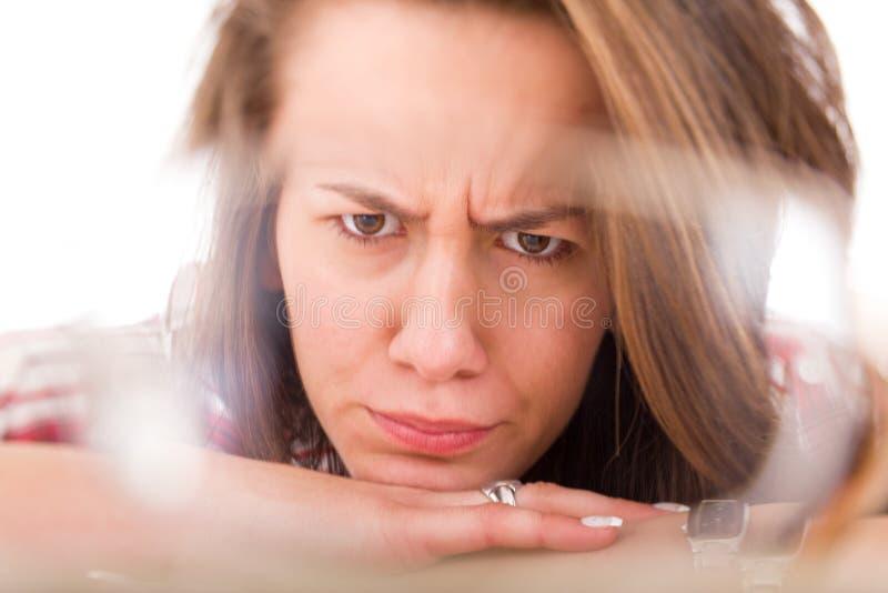 看通过玻璃的玻璃透镜的不满意的学生 库存图片
