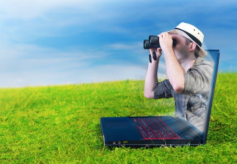 看通过从膝上型计算机的双筒望远镜的探险家 免版税库存照片