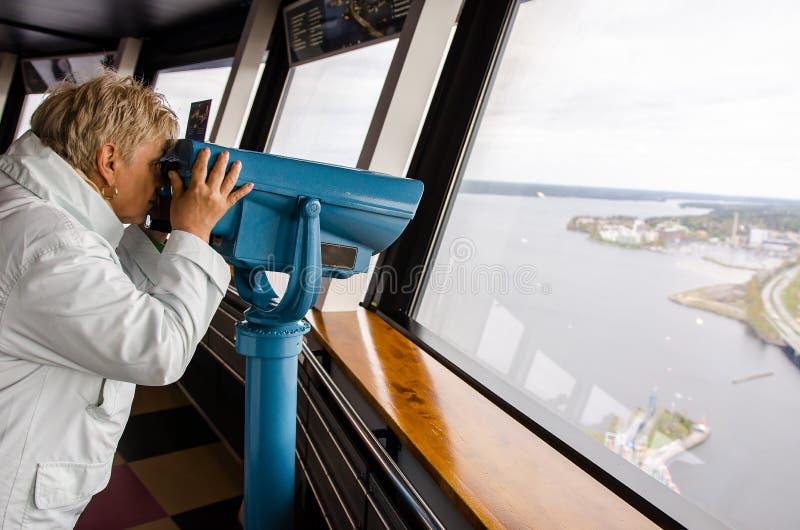 看通过从Nasinneula塔的双筒望远镜的妇女 库存照片