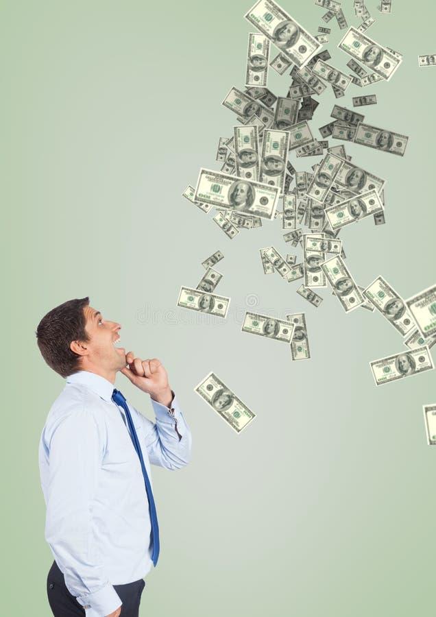 看金钱雨的愉快的商人反对绿色背景 库存照片