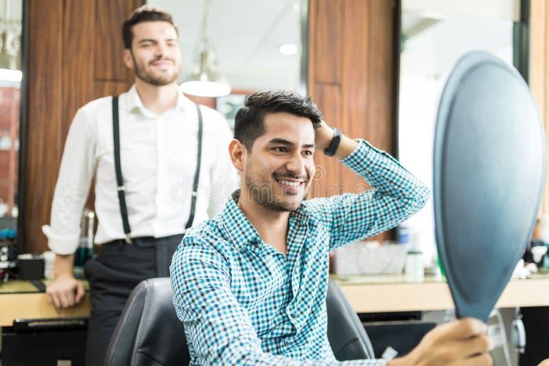 看镜子的满意的顾客在发型以后嘘 免版税库存照片