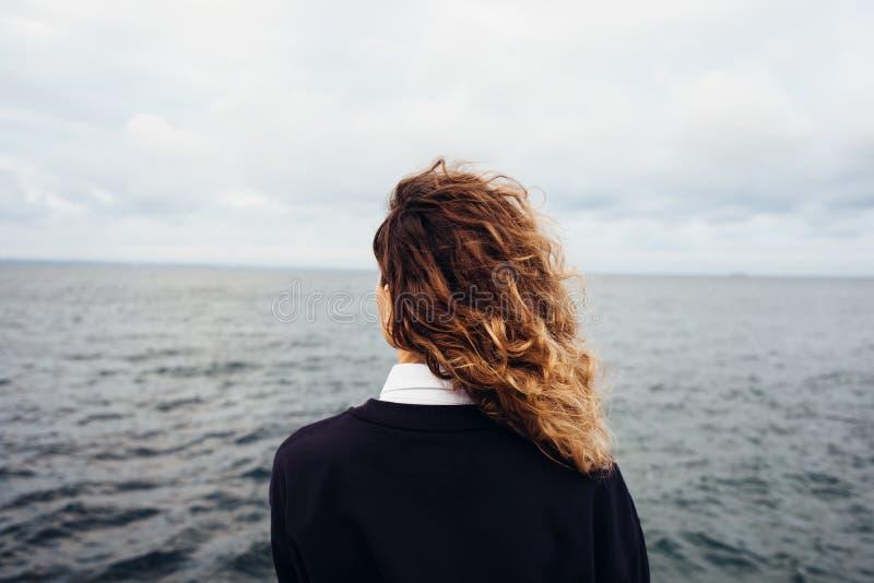 看阴暗天空和灰色海的年轻女人背面图 免版税库存图片
