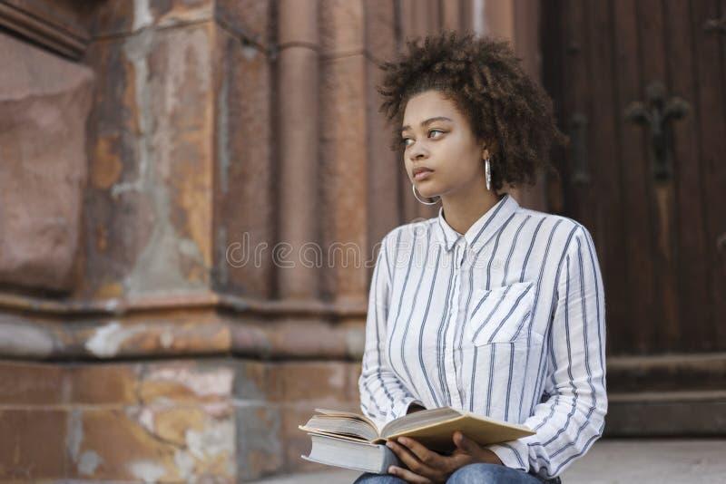 看非裔美国人的女孩坐街道和直接 在她的脚是书 库存图片