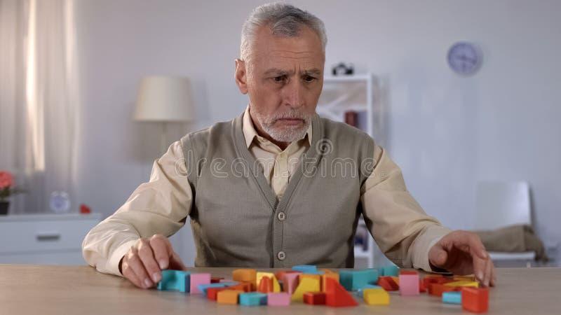 看颜色在桌,康复中心上的哀伤的领抚恤金者积木 免版税图库摄影