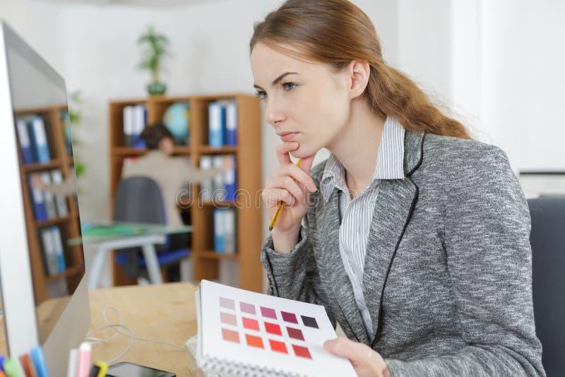 看颜色样片的书桌的设计师在办公室 免版税库存照片