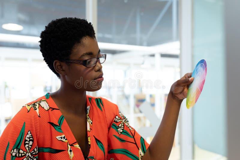 看颜色样片的女性图表设计师在办公室 库存照片