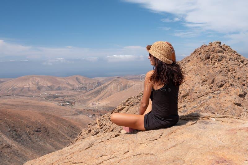看风景的轻松的女孩从山的顶端 免版税库存照片