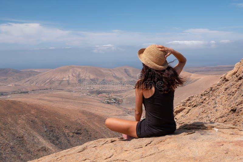 看风景的轻松的女孩从山的顶端 免版税图库摄影