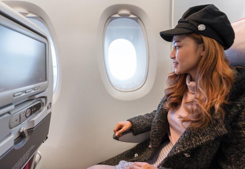 看飞机的窗口妇女在飞行中计时 库存照片