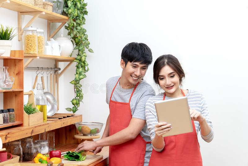 看食谱的可爱的年轻亚裔夫妇或学生和喜欢在家烹调食物在厨房里 男人和妇女gen的 免版税库存图片