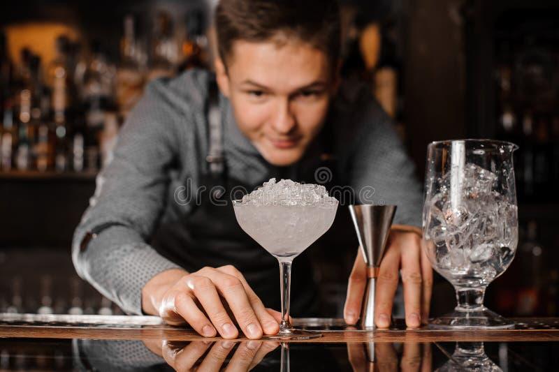 看鸡尾酒杯的年轻男服务员用冰填装了 库存照片