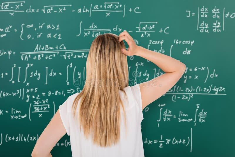 看黑板的迷茫的女孩在教室 免版税库存图片