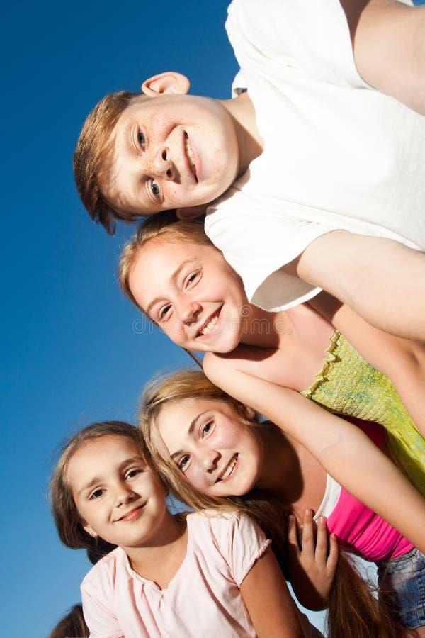 看从上面的四愉快的漂亮的孩子照相机晴朗的夏日和蓝天 看与滑稽的面孔a的照相机 图库摄影