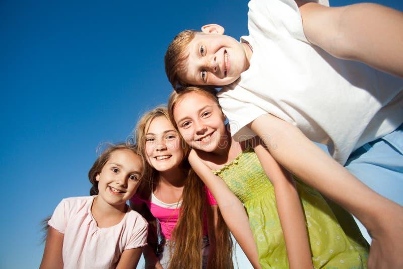 看从上面的四愉快的漂亮的孩子照相机晴朗的夏日和蓝天 看与滑稽的面孔a的照相机 免版税库存照片