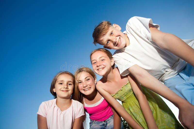 看从上面的四愉快的漂亮的孩子照相机晴朗的夏日和蓝天 看与滑稽的面孔a的照相机 免版税图库摄影