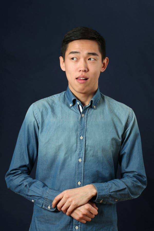 看年轻亚裔的人做面孔和斜向一边 免版税库存图片