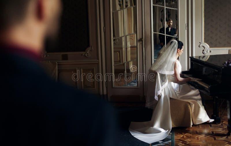 看他华美的新娘pla的典雅的时髦的英俊的新郎 免版税库存照片