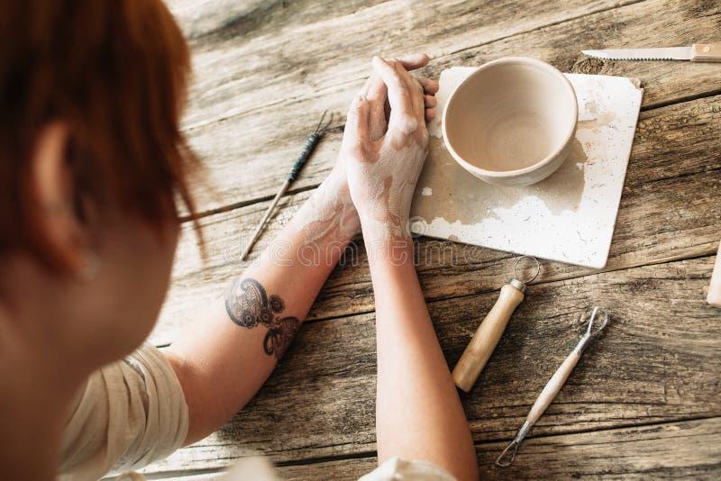 看黏土碗,顶视图的女性陶瓷工 免版税库存照片