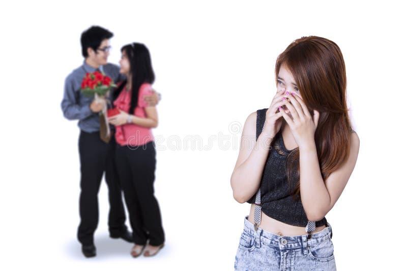看年轻夫妇的哀伤的十几岁的女孩 免版税库存图片