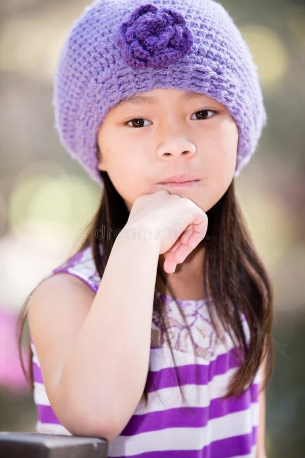 看直接入照相机的亚裔女孩,当户外时 免版税库存照片