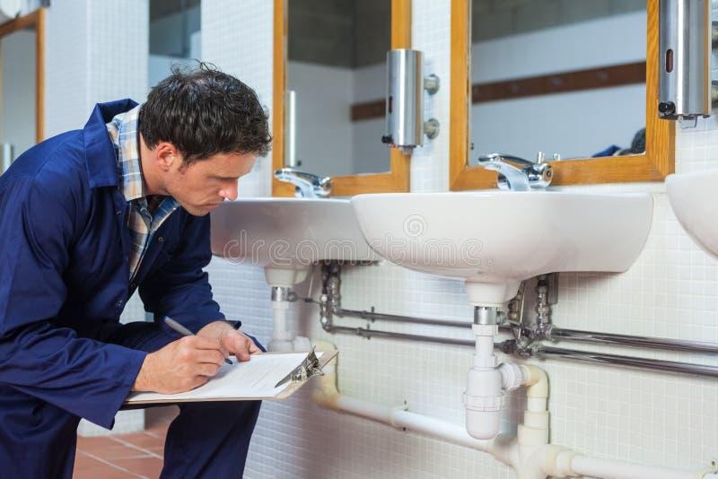 看水槽的英俊的水管工拿着剪贴板 免版税图库摄影