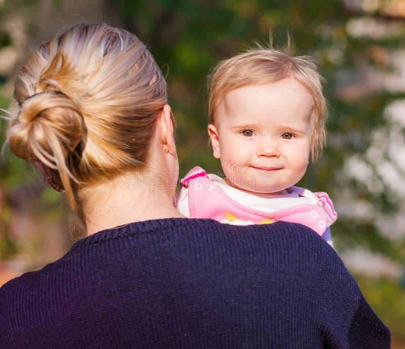 看从母亲的后面的逗人喜爱的女婴 图库摄影