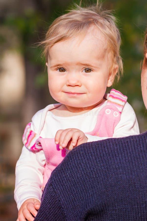 看从母亲的后面的逗人喜爱的女婴 免版税库存照片