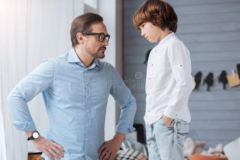看他的儿子的严肃的严密的人 免版税库存照片