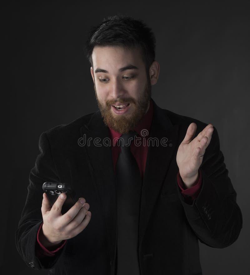 看他的电话的惊奇的商人 库存图片