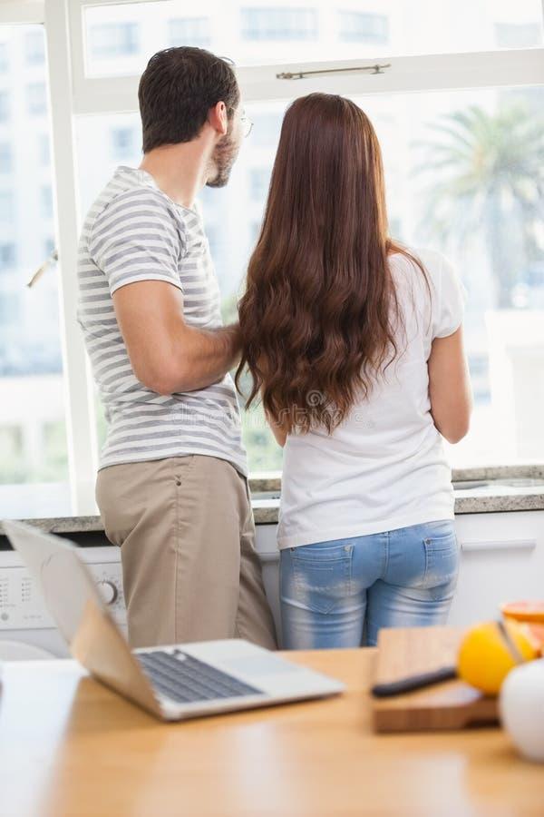 看他们的窗口的年轻夫妇 库存图片