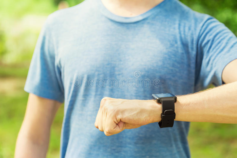 看他的smartwatch的公赛跑者 库存照片