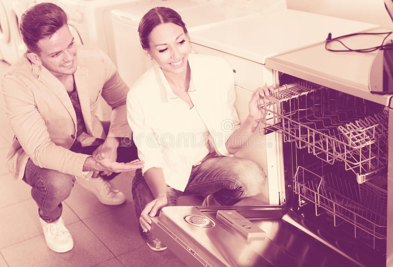 看洗碗机的愉快的家庭夫妇在商店 免版税库存图片