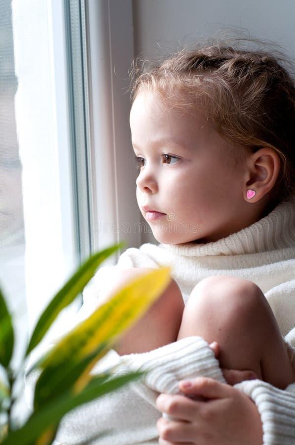 看从窗口的小女孩 免版税库存照片