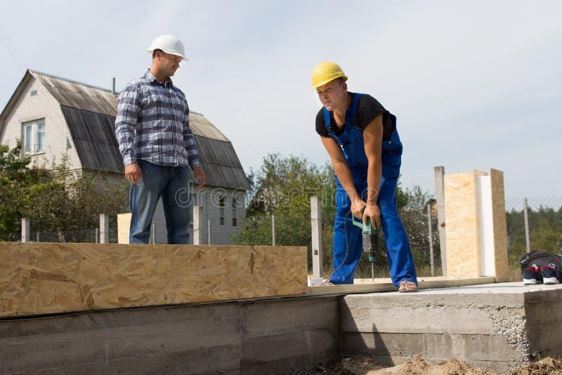 看建筑工人钻井的工程师 免版税库存图片