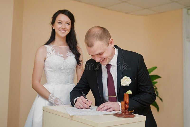看他美丽的新娘签署的婚礼记数器的时髦的新郎 免版税图库摄影
