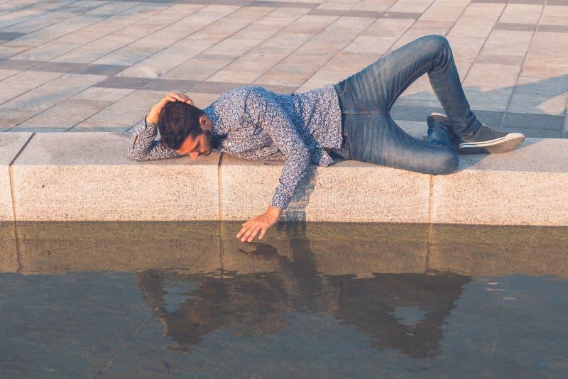 看他自己的年轻英俊的人在水中 免版税库存图片