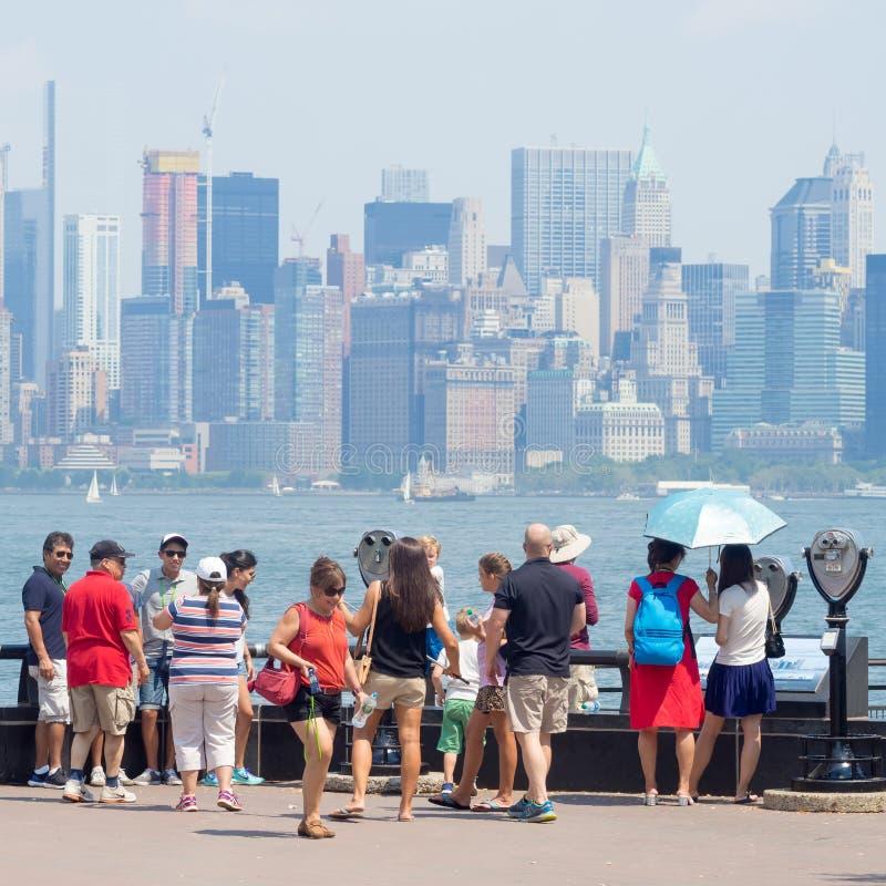 看从自由岛的游人曼哈顿地平线 库存图片