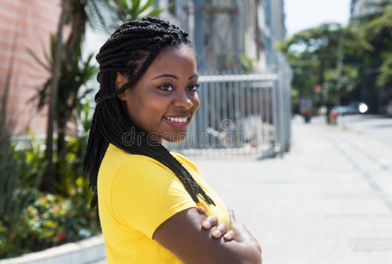 看黄色的衬衣的微笑的非裔美国人的妇女斜向一边 免版税库存照片