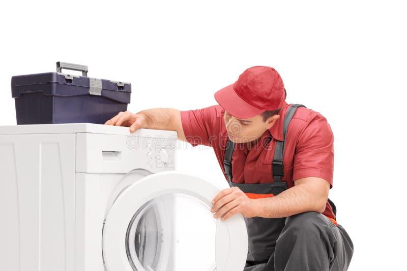 看洗衣机的年轻水管工 免版税图库摄影