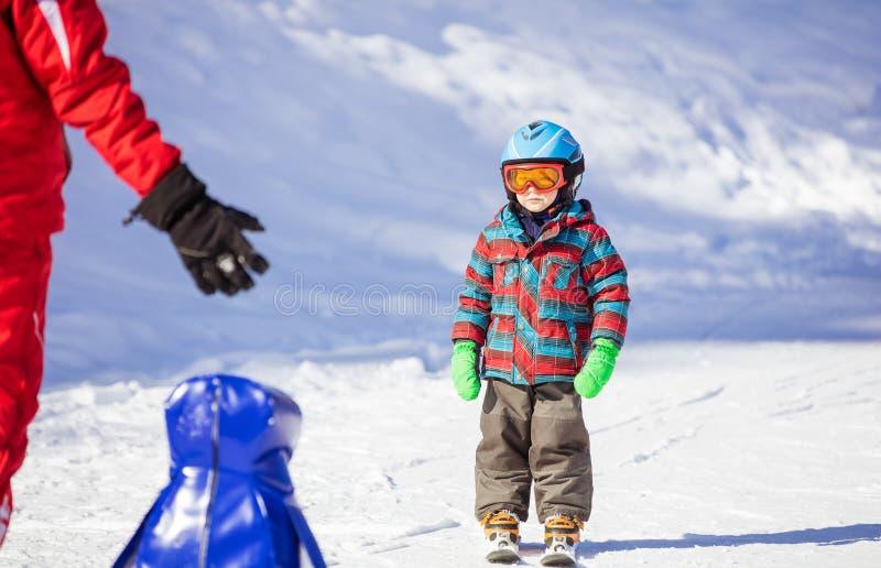 看滑雪辅导员的年轻滑雪者 免版税库存照片