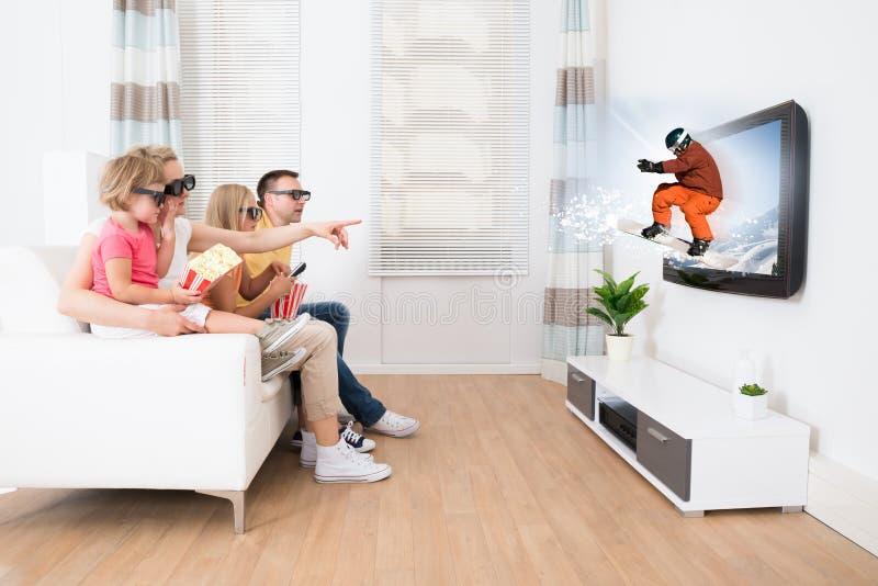 看3d电视的年轻家庭 免版税库存照片