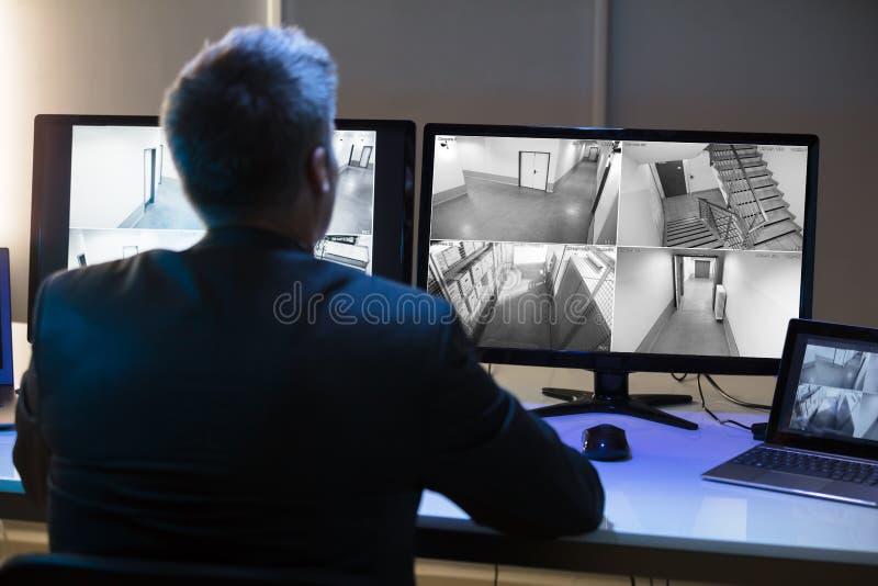 看CCTV照相机英尺长度的商人 库存图片