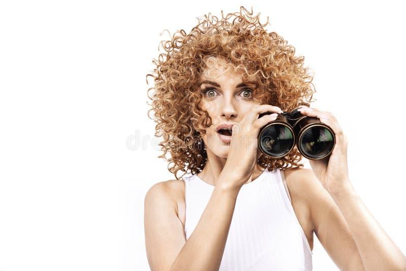 看throug的惊奇红头发人女孩双筒望远镜 库存照片