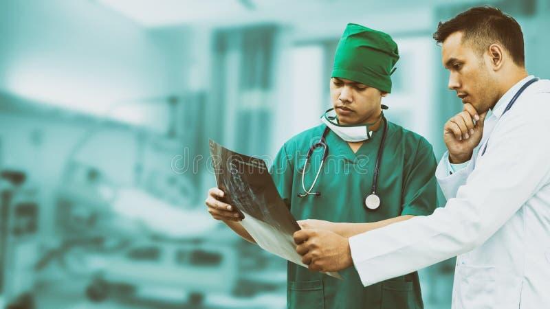 看X光片的医生和外科医生 免版税库存照片