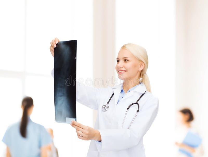 看X-射线图象的微笑的女性医生 免版税库存图片