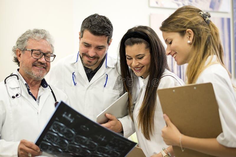 看X-射线的男性医生,当可爱的女性护理时 免版税库存图片